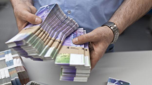 Ein Mann hält mehrere Bündel mit Tausend-Franken-Noten.