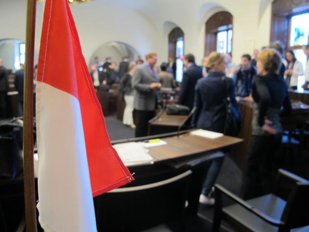 Blick in den Kantonsratssaal. Im Vordergrund die Flagge des Kantons, im Hintergrund verschwommen einige Kantonsräte.