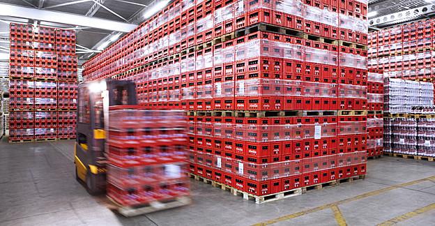 Hubstapler in Lagerhalle vor riesigen Rivella-Bergen