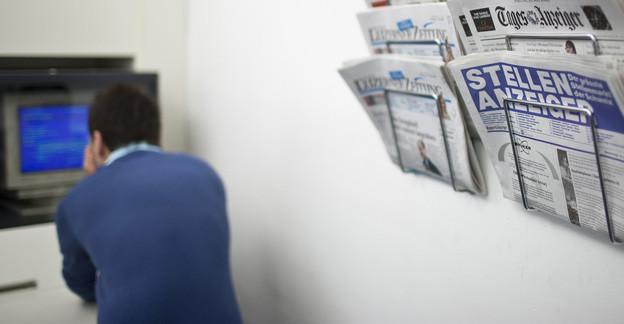 Stellenanzeiger in einem Ständer, dahinter ein Mann an einem PC auf einem regionalen Arbeitsvermittlungsamt.