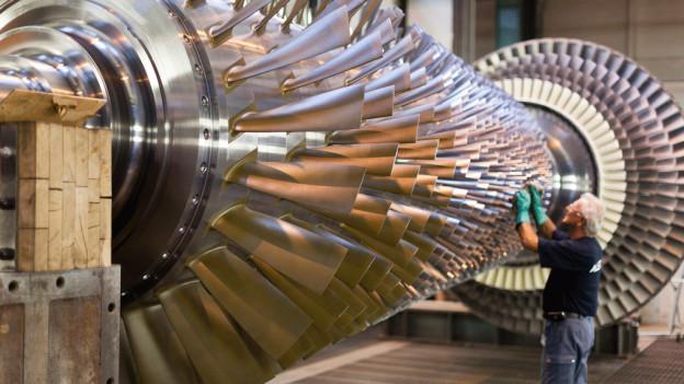 Ein Alstom-Mitarbeiter bearbeitet eine Turbine.