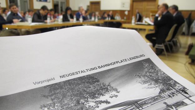 Die Unterlagen zum Projekt im Vordergrund. Im Hintergrund der Einwohnerrat von Lenzburg.