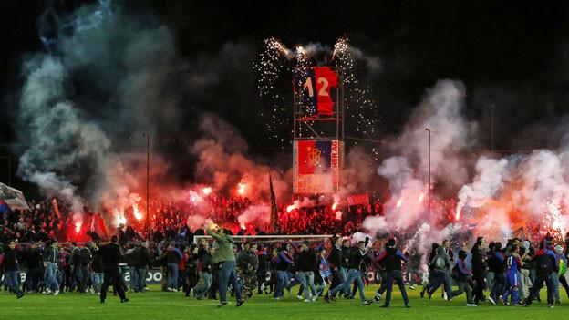 Das Brügglifeld mit Fans auf dem Rasen und zahlreichen roten Pyrofackeln.