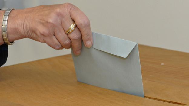 Eine alte Frau legt einen Stimmzettel in die Urne.