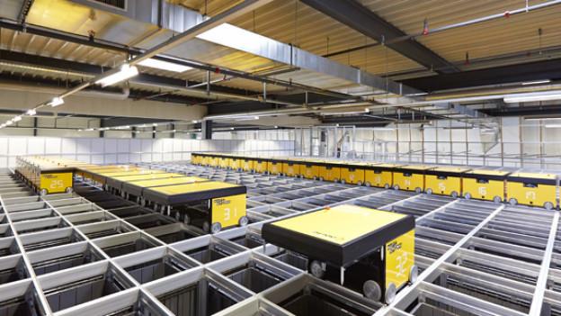 Gelbe Roboterwagen auf Schienen, darunter Löcher mit grauen Behältern.
