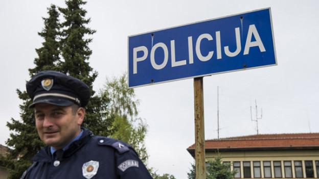 Ein serbischer Polizist vor einer Polizeistation