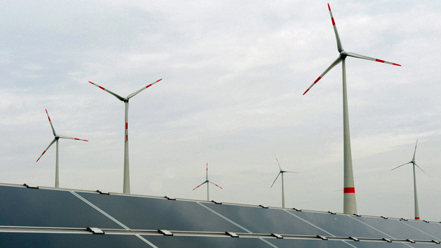 Im Vordergrund Solaranlagen, im Hintergrund Windkraftanlagen.