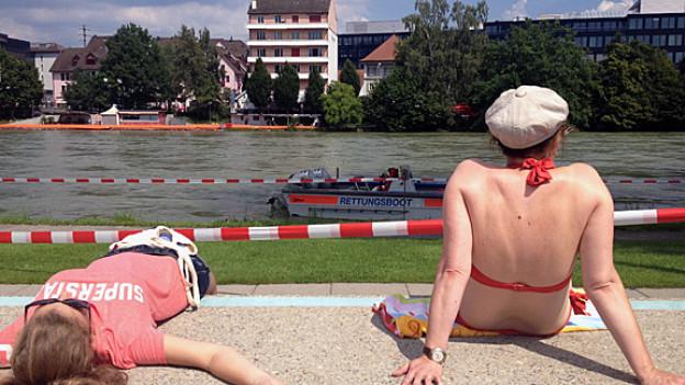 Zwei Frauen am Flussrand, eine davon im Bikini