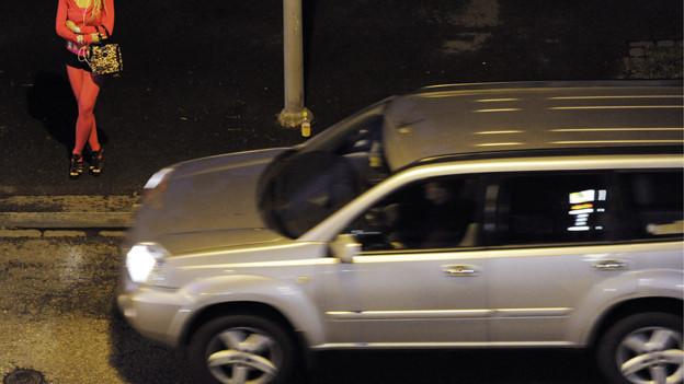 Ein Auto fährt an einer Prostituierten vorbei.