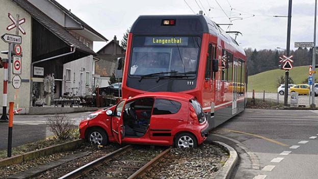 Regionalzug mit kaputtem Auto nach Unfall bei Bahnübergang