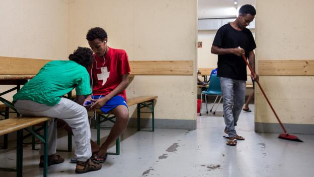 Asylbewerber sitzen auf Bänken, einer putzt den Boden
