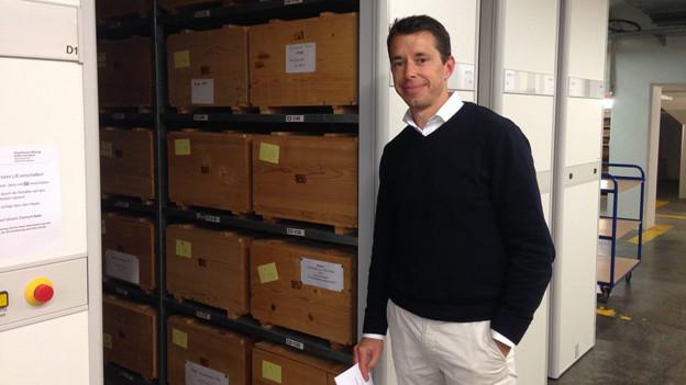 Kantonsarchäologe Georg Matter vor den Holzkistchen, wo der Hausbock sich besonders wohl fühlt.