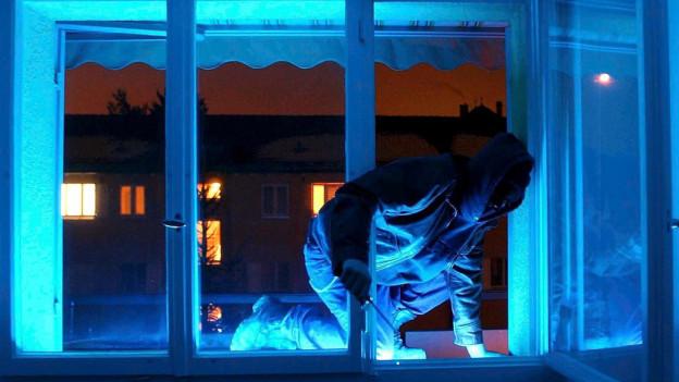Mann mit Maske bricht Fenster auf