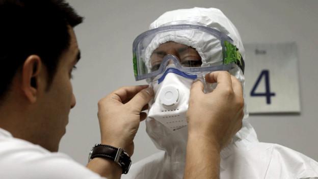 Ein Spitalmitarbeiter kontrolliert den Schutzanzug eines anderen.