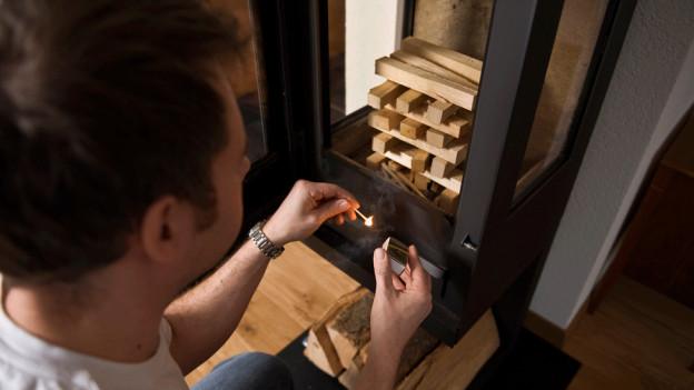 Mann zündet Holz im Schwedenofen an.