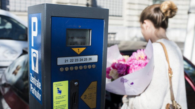 Parkuhr in einer Stadt, dahinter Frau mit Blumenstrauss