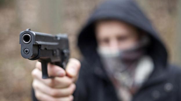 Maskierter Mann mit Pistole