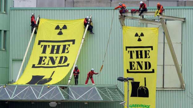 """Aktivisten hängen Plakate mit """"The Ende"""" am AKW auf."""