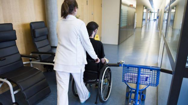 Eine Krankenschwester schiebt einen Patienten im Rollstuhl durch einen Gang.