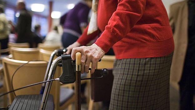 Eine Frau mit Rollator läuft vor Stuhlreihe durch