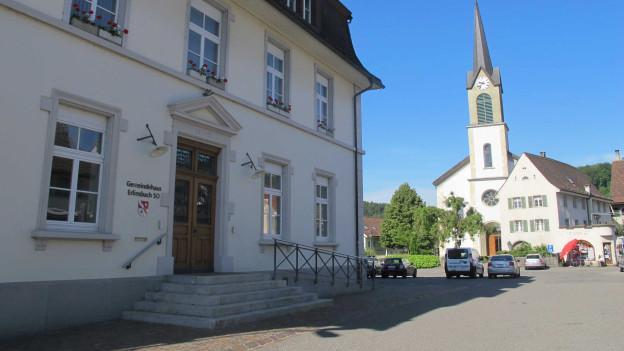 Gemeindehaus von Erlinsbach im Kanton Solothurn mit der Kirche im Hintergrund.