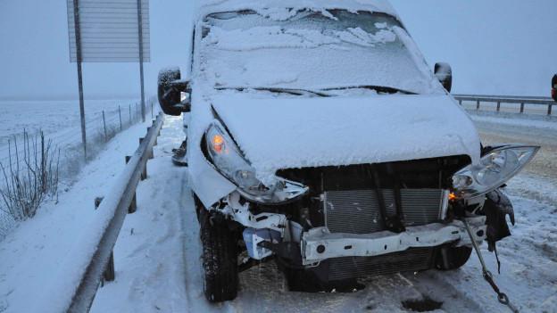 Ein Van steht eingeschneit mit eingedrücktem Kotflügel auf dem Pannenstreifen der A1.