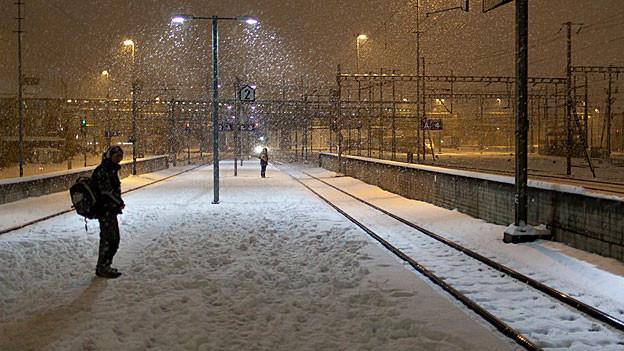 In der Kälte am Bahnhof stehen und auf den Zug warten