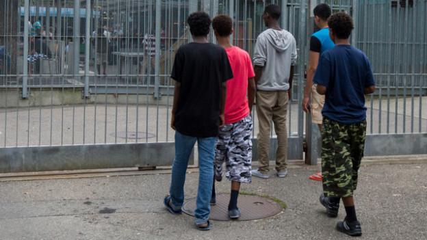 Mehrere junge Asylbewerber stehen vor Gitter