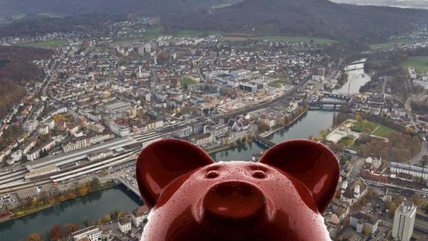 Im Vordergrund ein rotes Sparschwein, im Hintergrund eine Luftaufnahme der Stadt Olten.