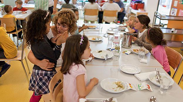 Kinder und Betreuerin beim Mittagessen