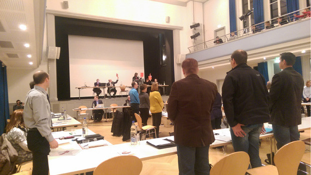 Mehrere Personen stehen an Pulten in einem Saal.