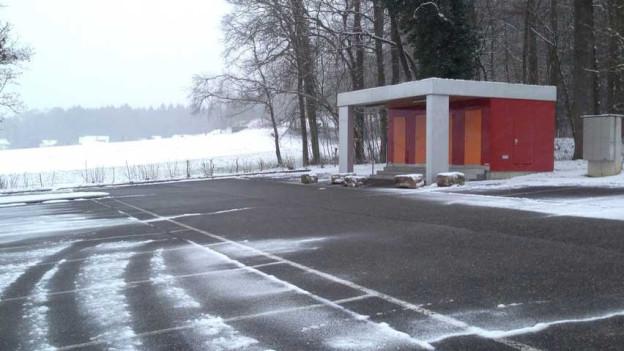 Bild vom Parkplatz mit dem Gebäude, in dem die sanitären Anlagen untergebracht sind.