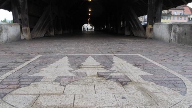 Stadtwappen in Stein auf Holzbrücke.