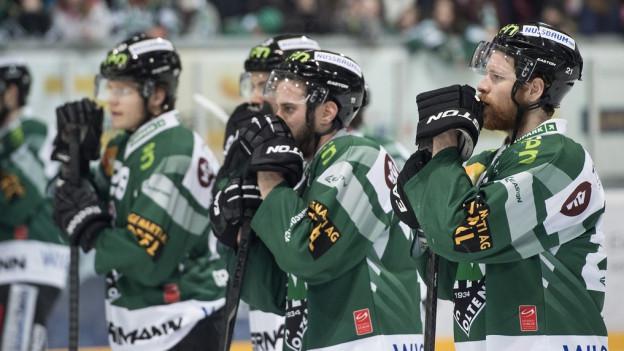 Traurige Gesichter nach dem Spiel, während die Spieler auf dem Eis stehen.