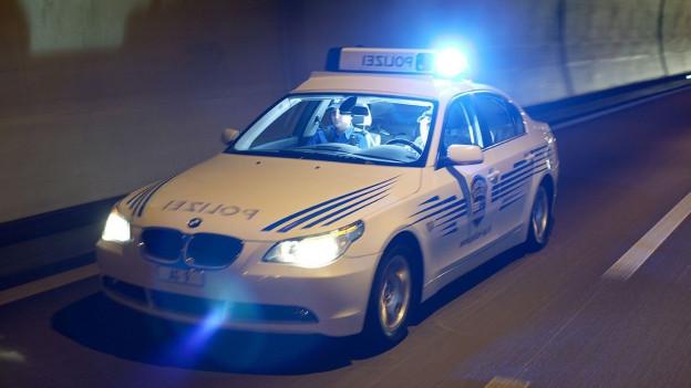 Polizeiauto fährt mit Blaulicht durch einen Tunnel