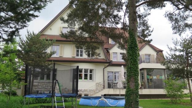 Blick auf ein betreutes Wohnheim, im Vordergrund ein Baum und ein Pool.