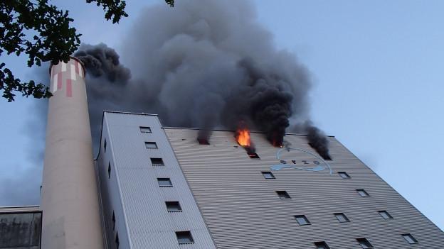 Dunkler Rauch und Flammen schlagen aus dem obersten Stockwerk.