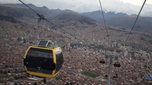 Gelbe Gondel vor der bräunlichen Skyline von La Paz.