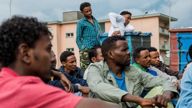 Eritreer vor einer Asylunterkunft.
