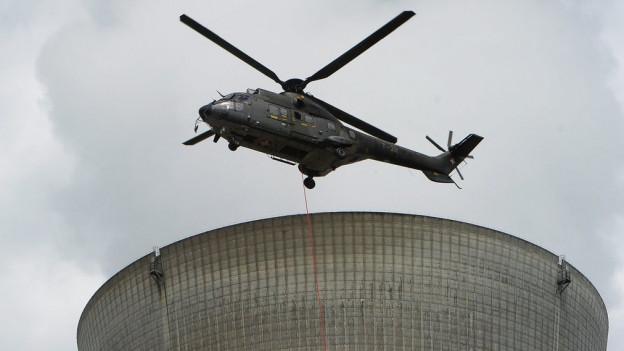 Helikopter über Kühlturm.