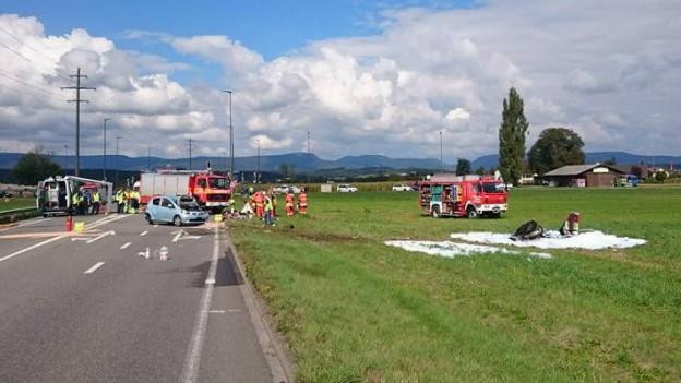 Unfallstelle auf einer Wiese mit einer Strasse daneben, zu sehen sind mehrere Feuerwehr- und Polizeifahrzeuge.