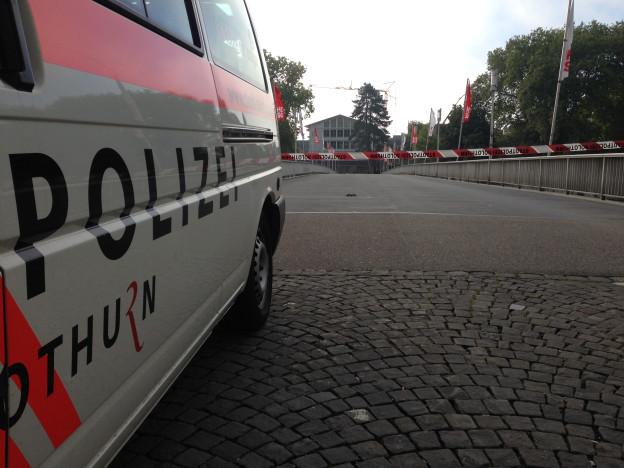 Ein Einsatzwagen der Kantonspolizei Solothurn steht vor der abgesperrten Kreuzackerbrücke. Im Hintergrund das von der Bombendrohung betroffene Berufsschulhaus.
