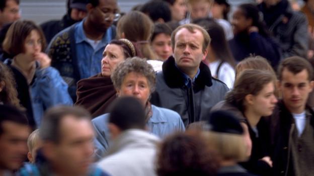 Eine Menschenmenge bewegt sich auf kleinem Raum innerhalb einer Stadt.