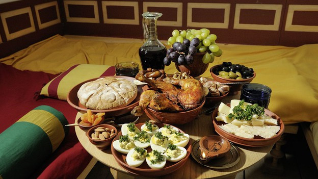 Römische Tafel mit Trauben, Brot und Käse.