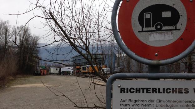 Vorne: Tafel mit Verbot für Camper. Hinten: Bauwagen der Wagabunten.