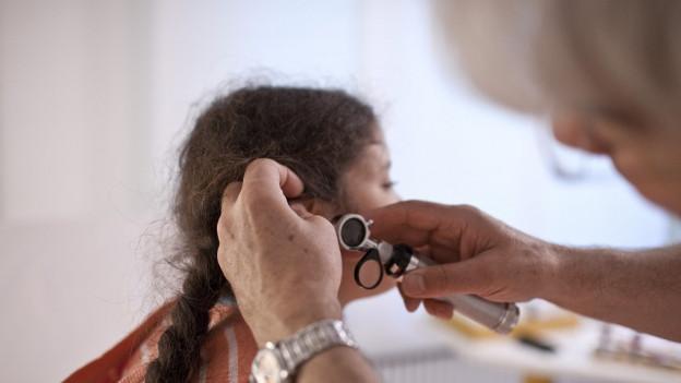 Arzt schaut ins Ohr eines Mädchens.