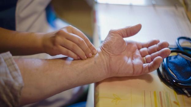 Hand fühlt einem Arm den Puls.