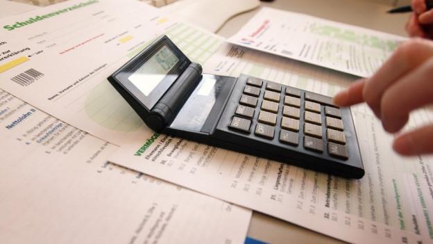 Taschenrechner auf wild verteilten Steuerunterlagen.