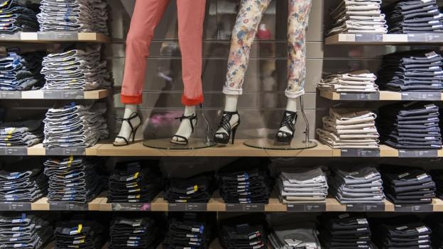Jeans gestapelt in Regal. Dazu zwei Beine von Schaufensterpuppen mit bunten Hosen.