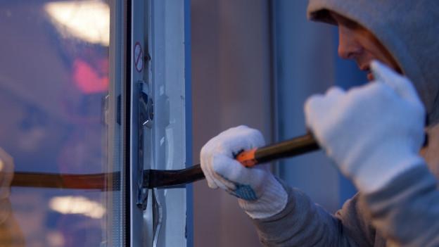Mann mit weissen Handschuhen wuchtet mit Brecheisen ein Fenster auf.